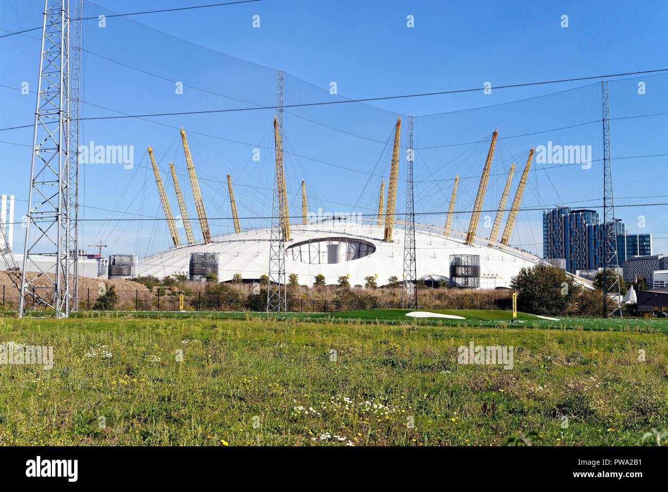 The O2 dome with a golf driving range and large safety netting in the foreground ,Greenwich Peninsula London England UK - Stock Image