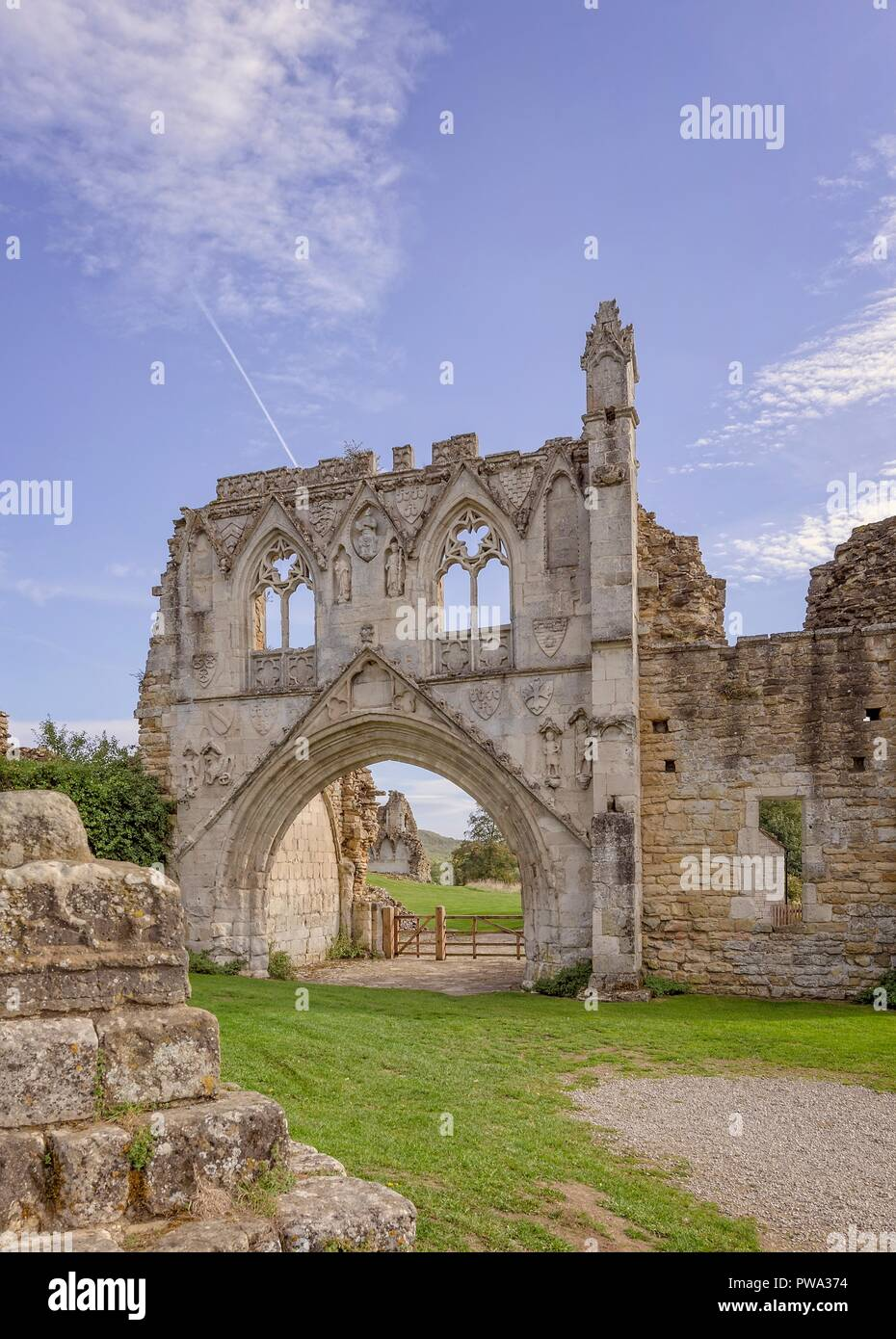 The ruins of Kirkham Priory in North Yorkshire.  The gateway with its carvings largely intact standing under a blue sky. Stock Photo
