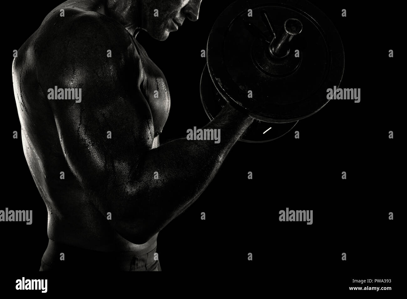 Athletic man training biceps at the gym. black and white effect - Stock Image