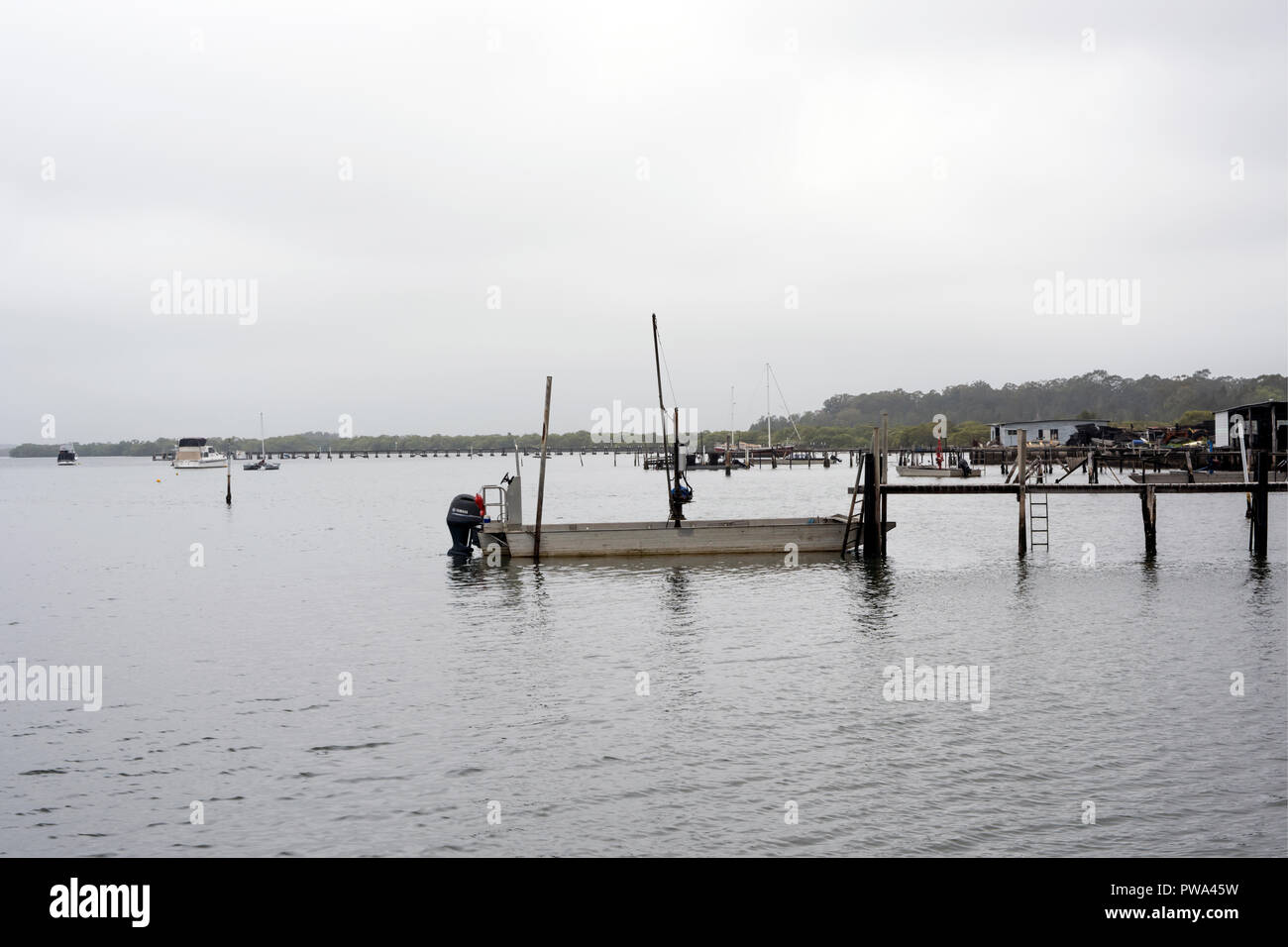 Aluminium Flat bottomed fishing boat tied up at old wooden pier. - Stock Image