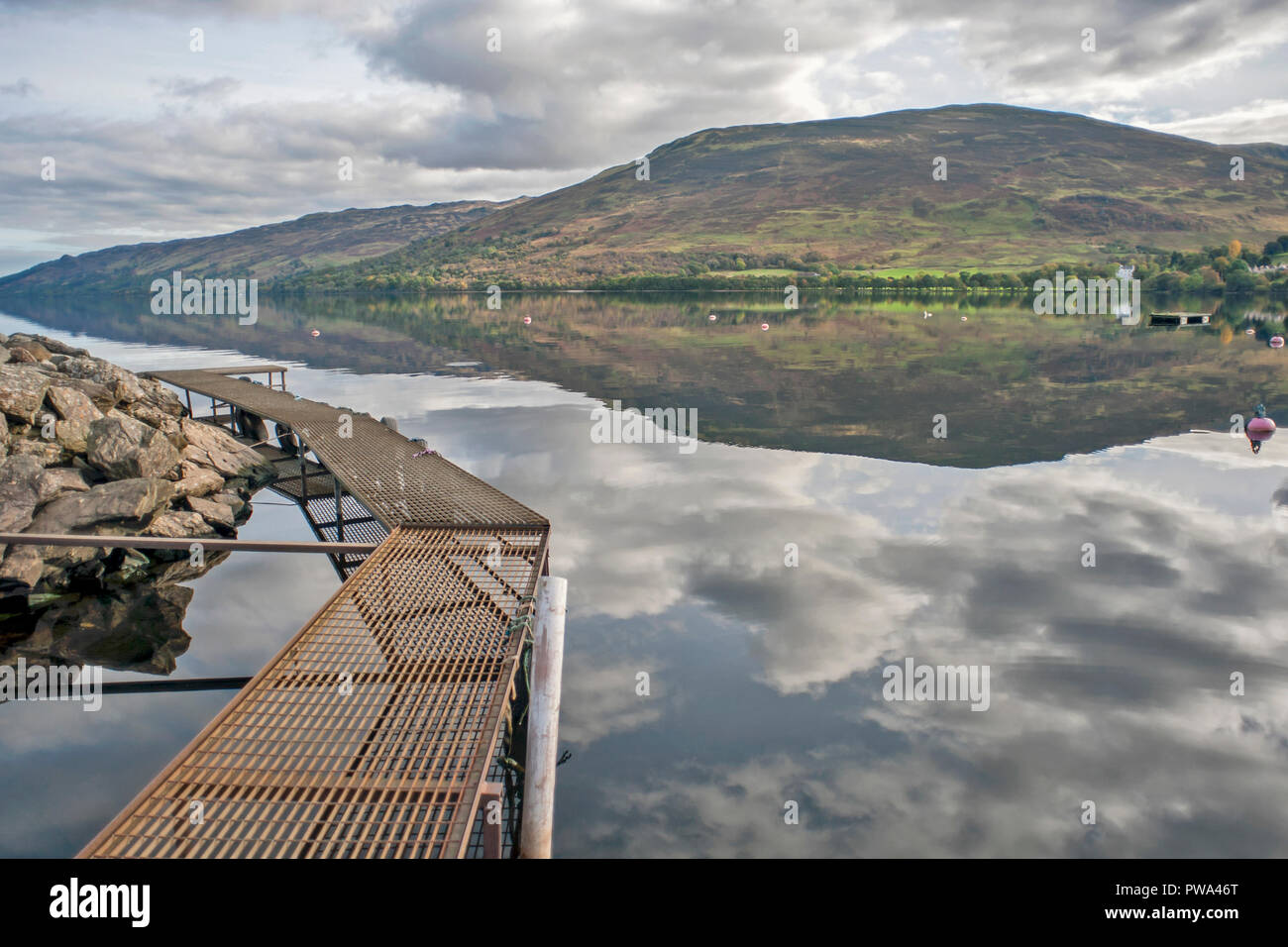 Views across Loch Earn, Perth and Kinross and Stirling, Scotland  on a calm day with reflections of the sky in the water - Stock Image