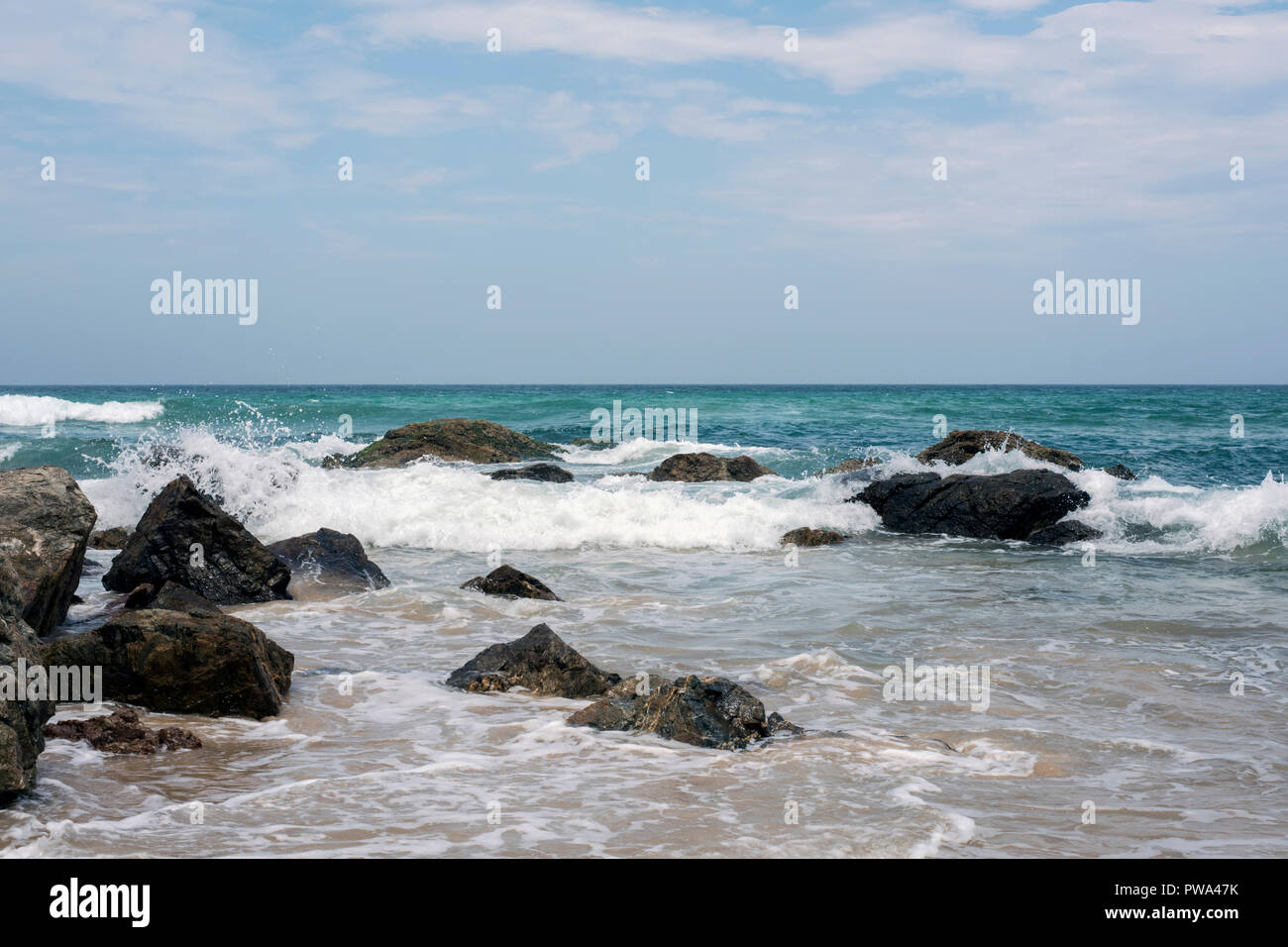 Waves lapping against rocks on the seashore in fine weather. - Stock Image