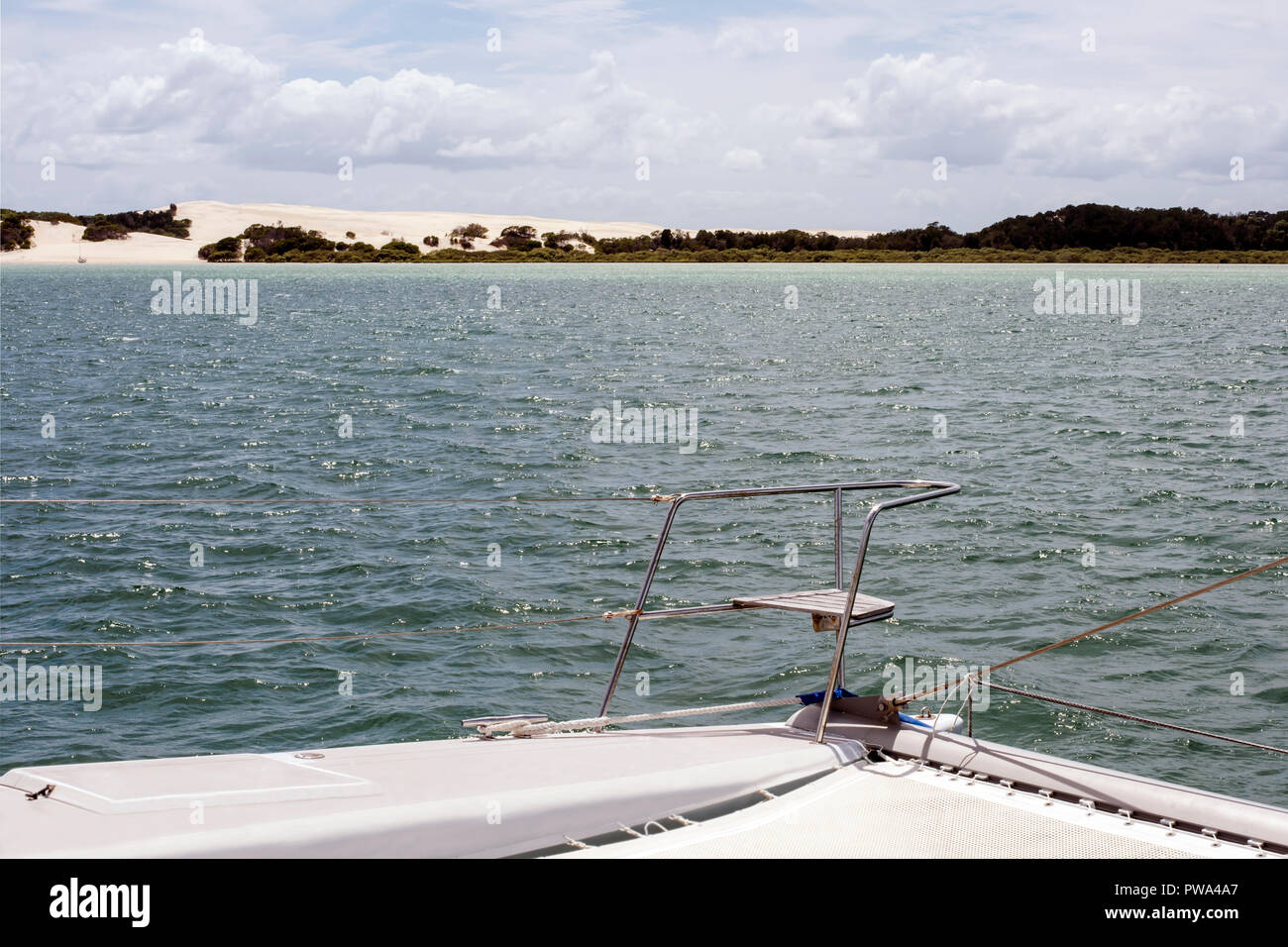 Sand dunes on Moreton Island, Queensland, Australia viewed with pulpit seat of approaching catamaran in  foreground. 'Best seat in the house!' - Stock Image