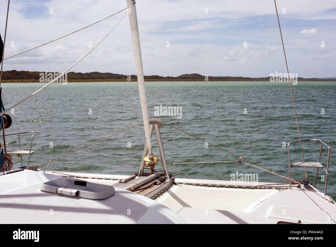Approaching a tree lined island from the sea with the bow of the yacht in the foreground, suggesting the promised land. - Stock Image
