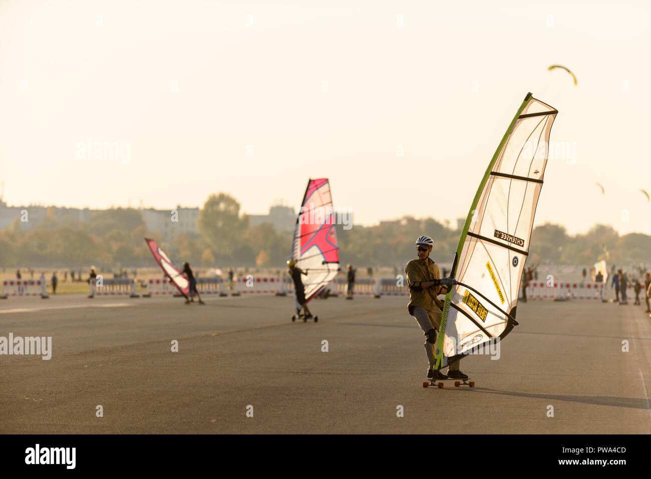 Wind skaters are at the Tempelhofer field. The good weather in October brings many visitors to the park at the former Tempelhof Airport. - Stock Image