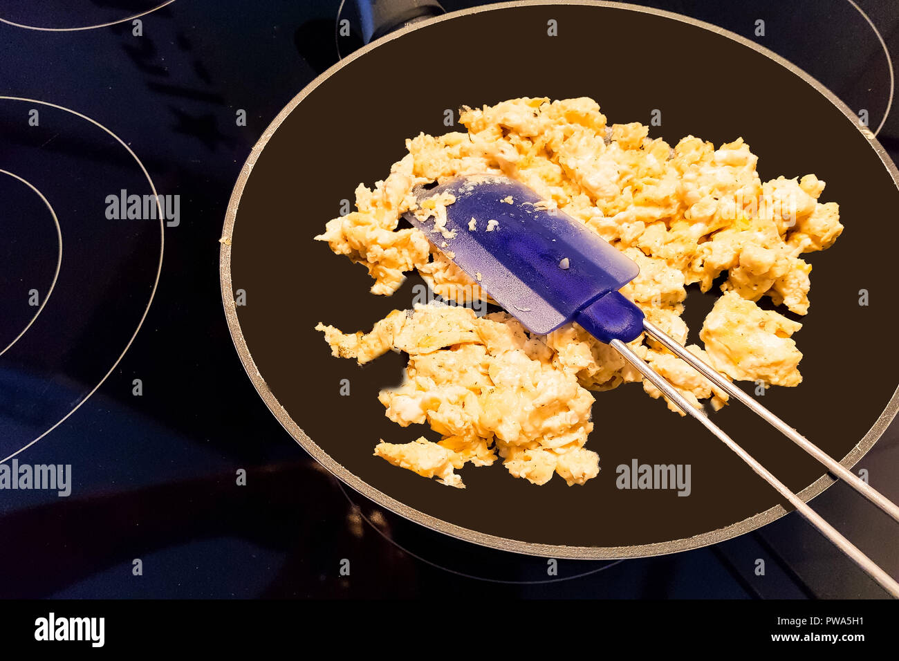 Scrambled eggs in a pan on an induction hob - Stock Image