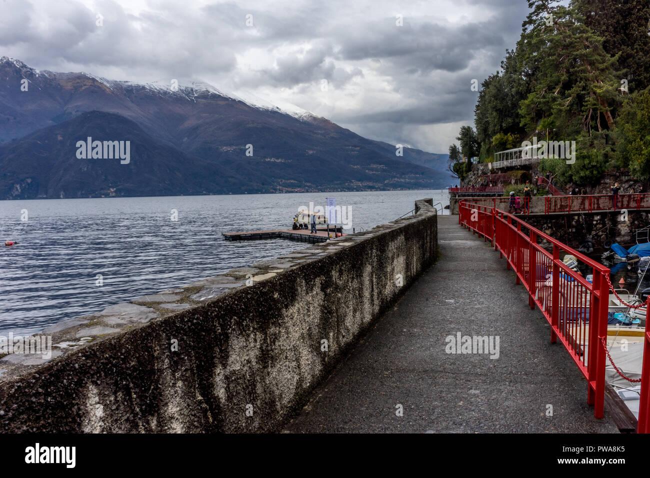 Varenna, Italy - March 31, 2018: People walk across a bridge on Lake Como at Varenna, Italy - Stock Image