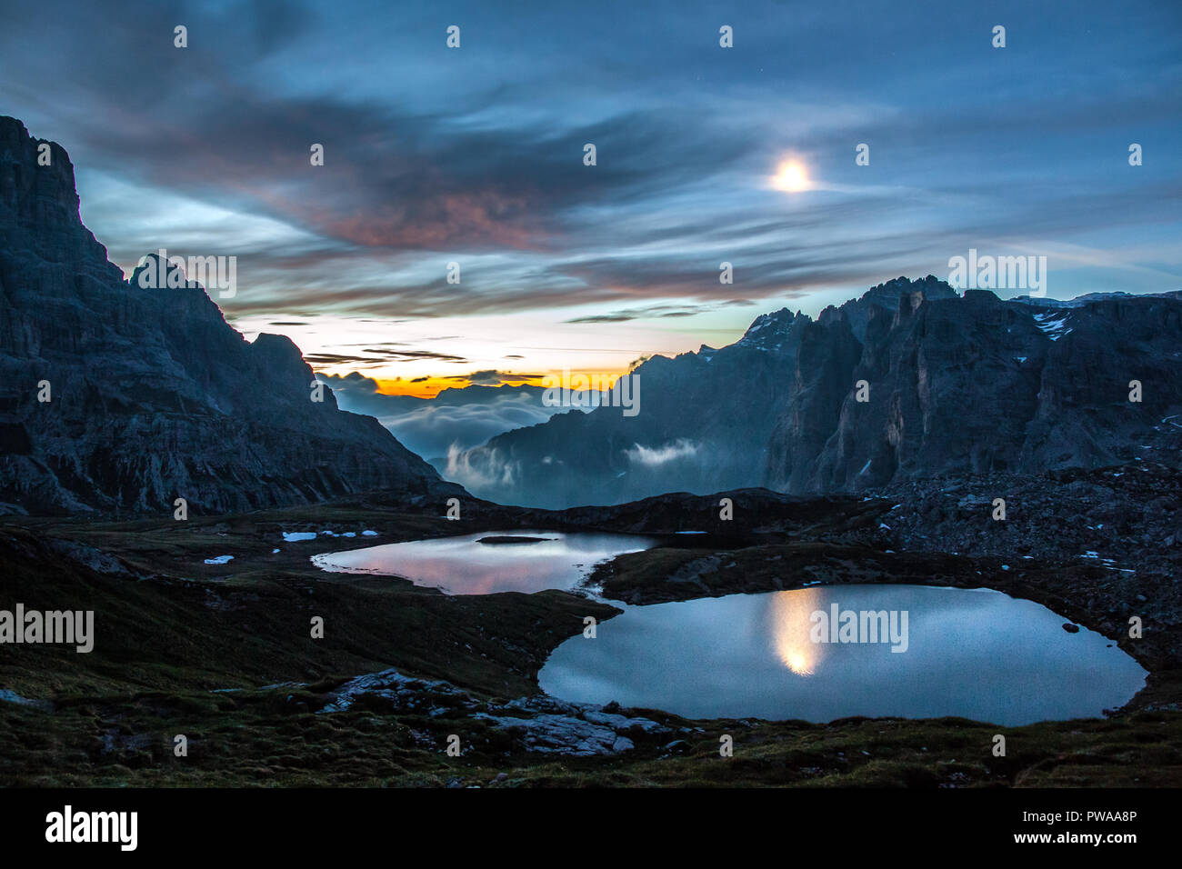 Moonlight and dusk lights reflected in Laghi dei Piani, South Tyrol, Italy - Stock Image
