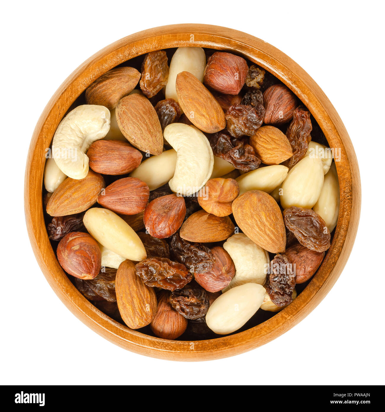 Nuts and raisins in wooden bowl. Snack mix of dried almonds, hazelnuts, cashews and raisins. Trail mix. Edible, raw, organic and vegan. - Stock Image
