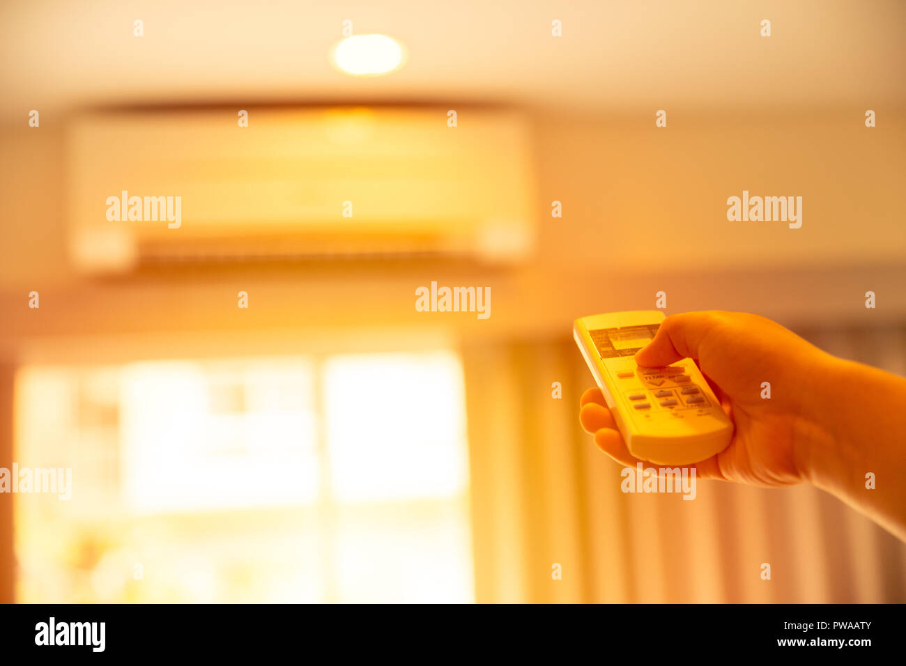 hand adjust AC temperature with remote control to wall type air conditioning home cooling system in very hot summer day - Stock Image
