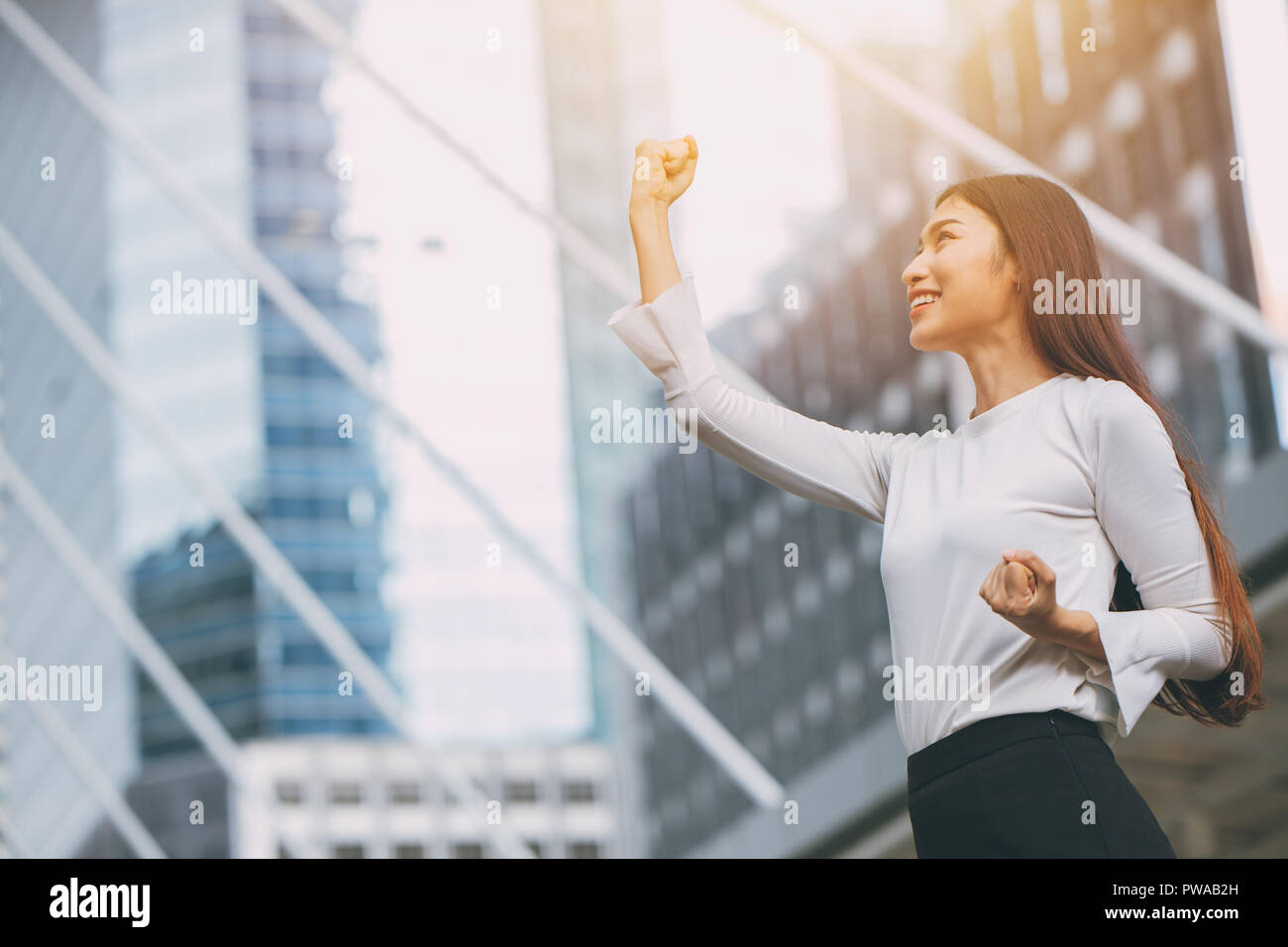 winner successful business employee girl rise up fist hand with city office building background - Stock Image