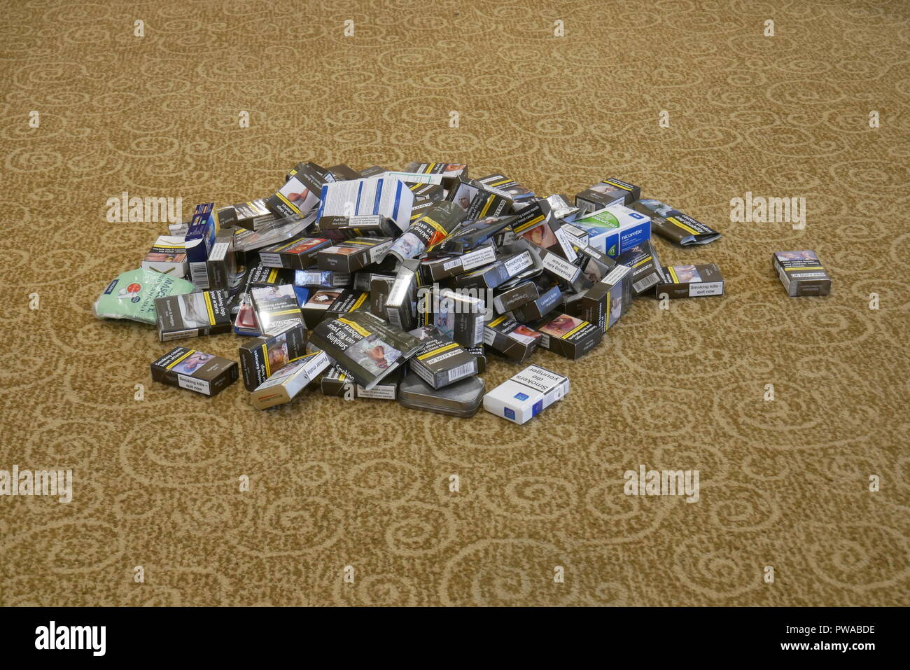 A pile of discarded nicotine delivery systems including tobacco products and Nicotine Replacement products - Stock Image