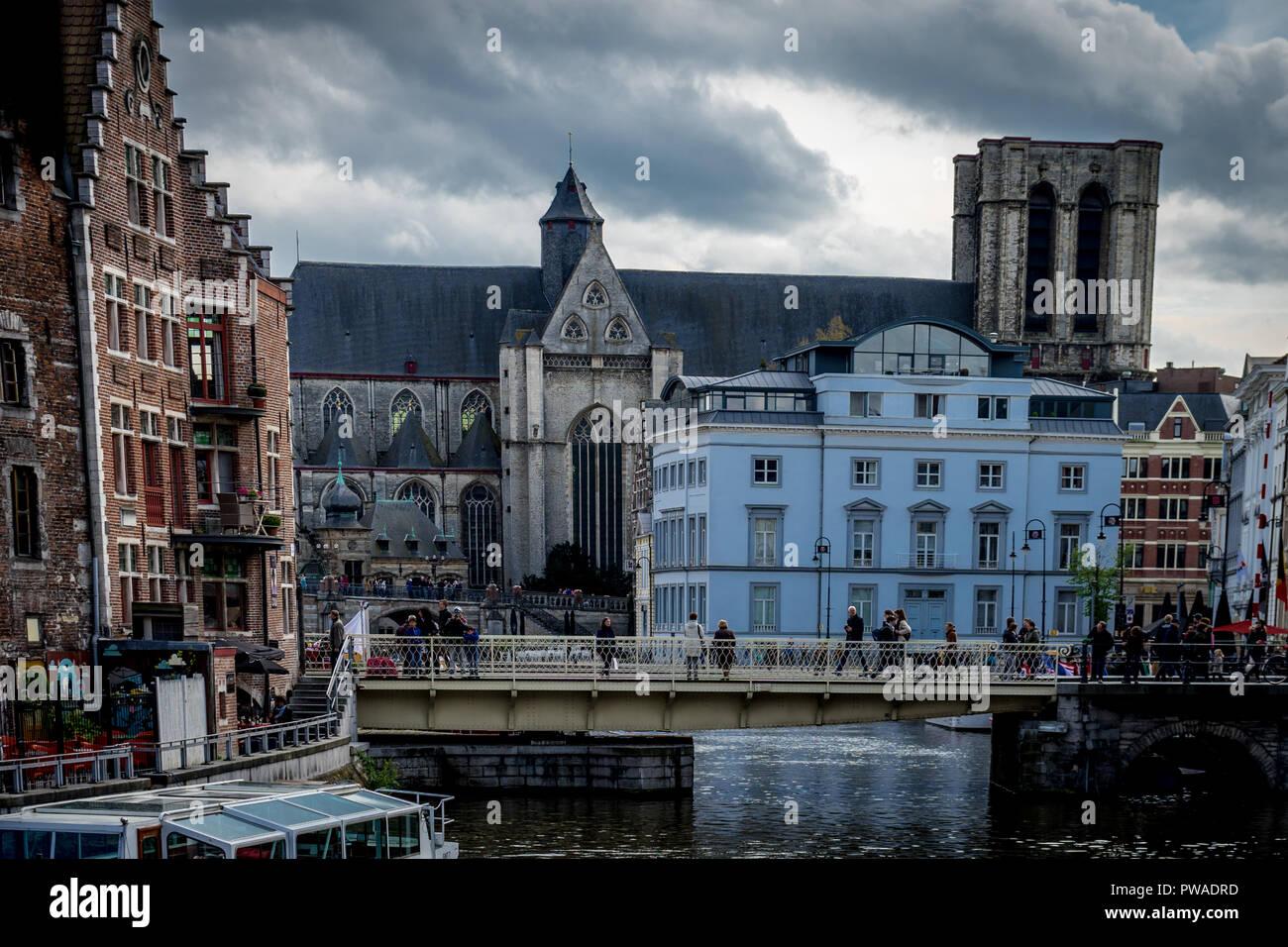 Ghent Belgium - April 15 : Toursists walk across the bridge near the Saint Michael's Church in Ghent, Belgium, Europe - Stock Image