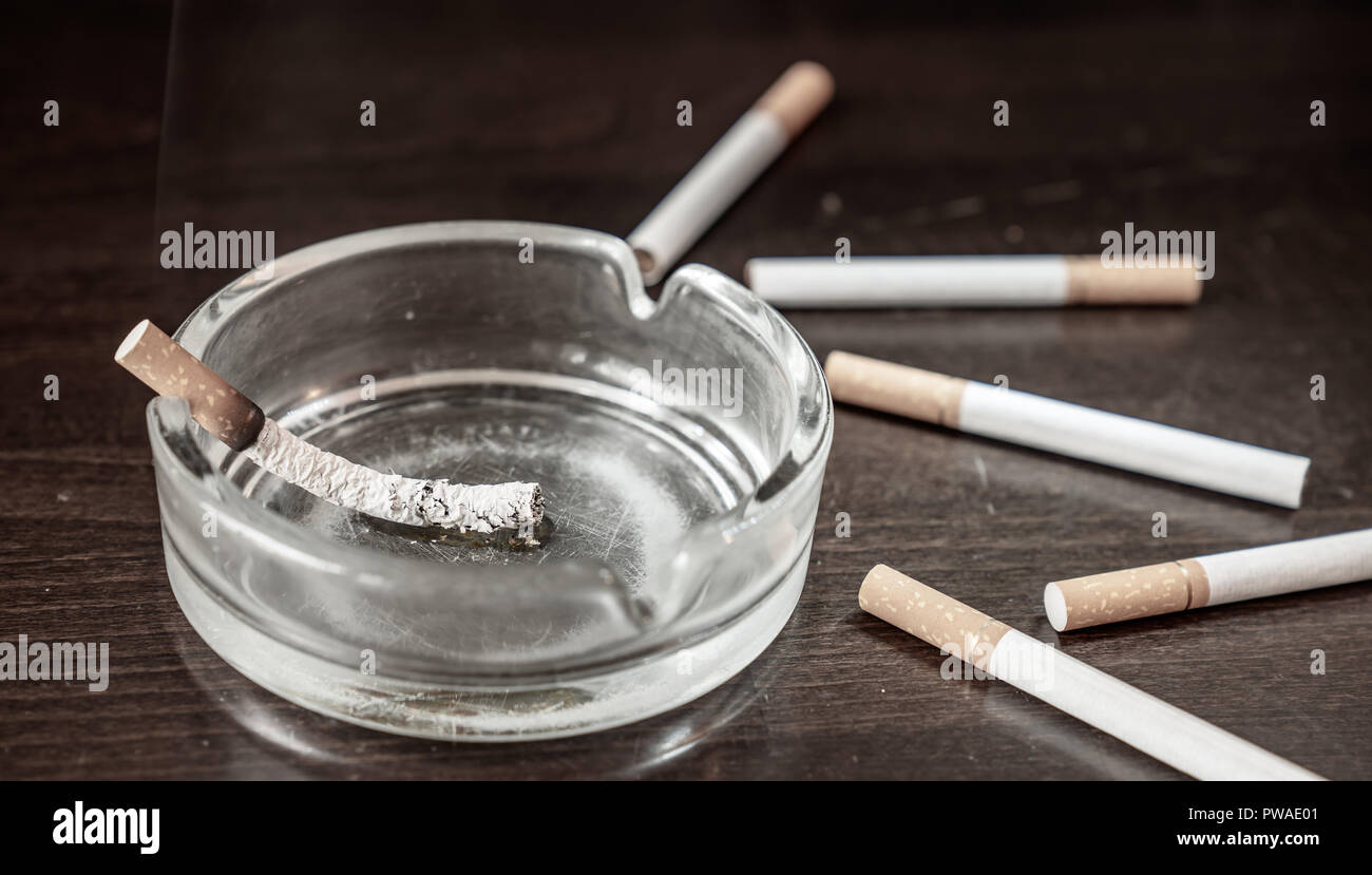 A glimmering cigarette burns in an ashtray on a table with cigarettes around it - Stock Image