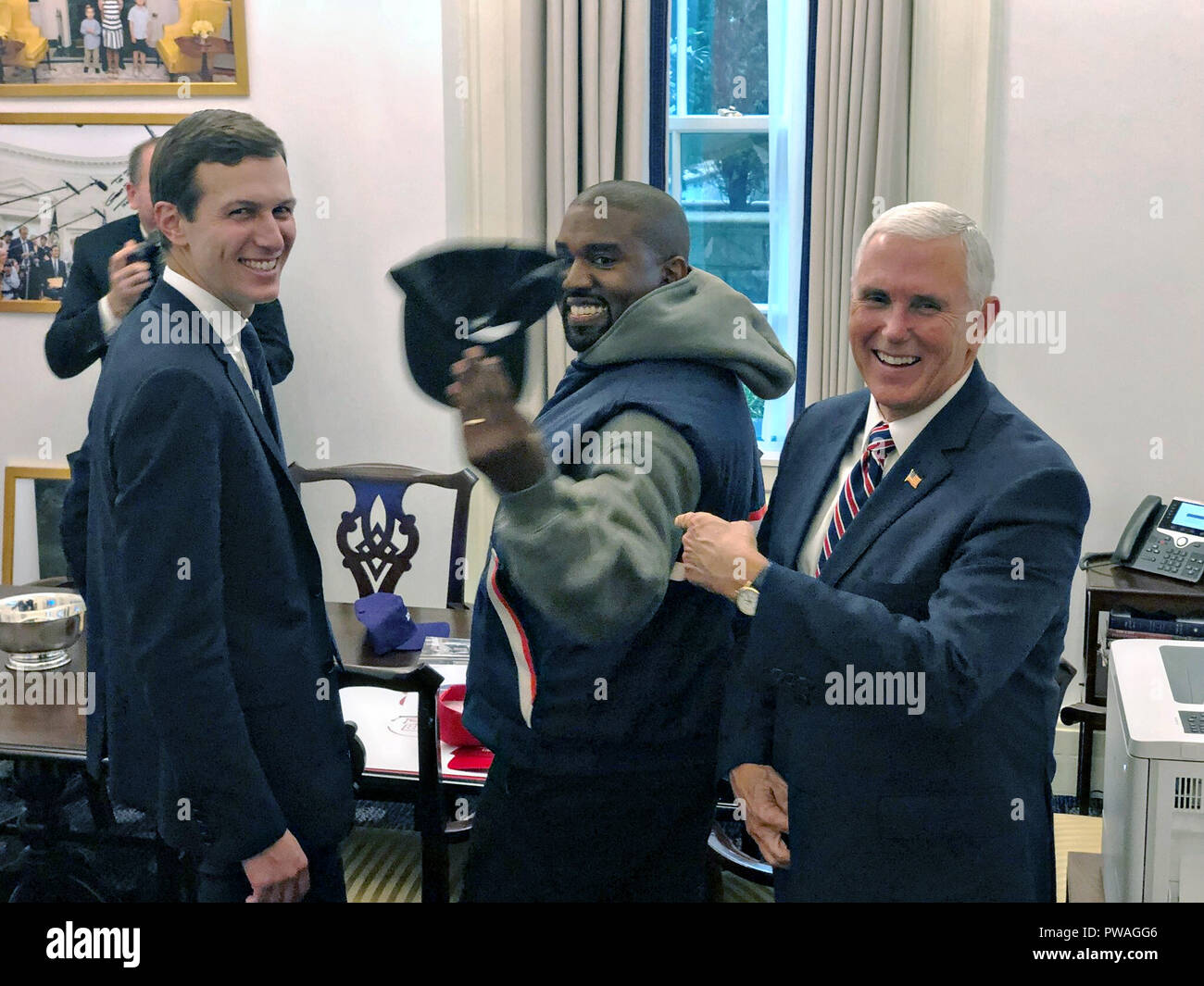 U.S Vice President Mike Pence laughs as he jokes with performer Kanye West, center, as Presidential adviser Jared Kushner, left, looks on in the outer Oval Office of the White House October 11, 2018 in Washington, DC. - Stock Image