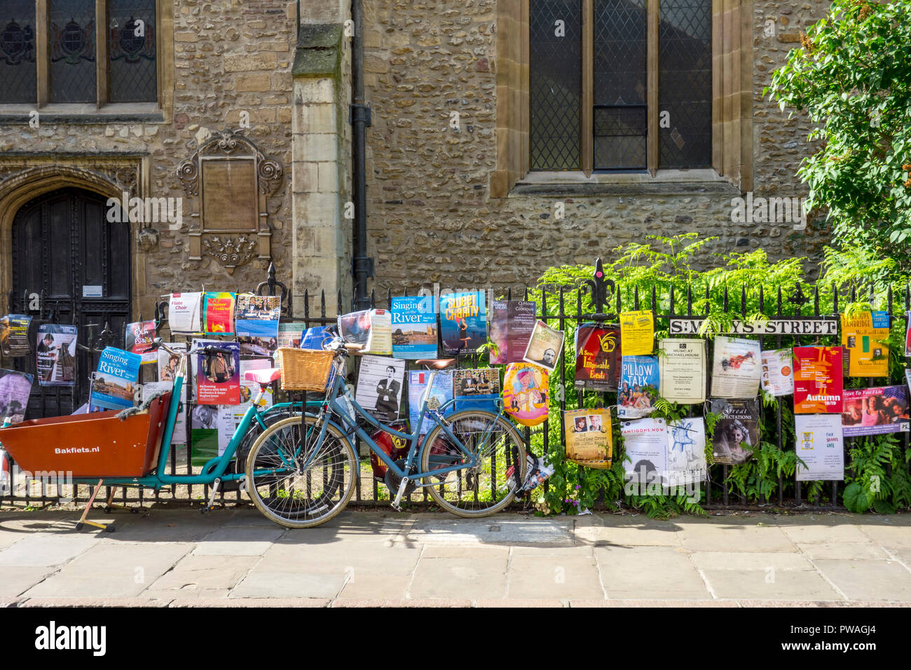 Bicycle chained to railings surrounded by posters or flyers outside Great St Mary's Church, Cambridge, UK - Stock Image