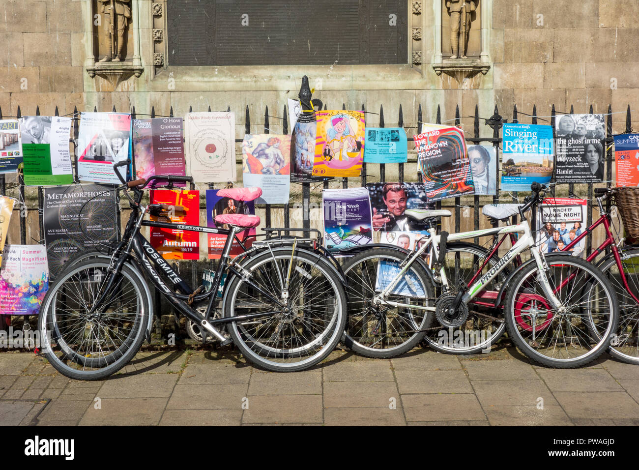 Bicycles chained to railings surrounded by posters or flyers outside Great St Mary's Church, Cambridge, UK - Stock Image