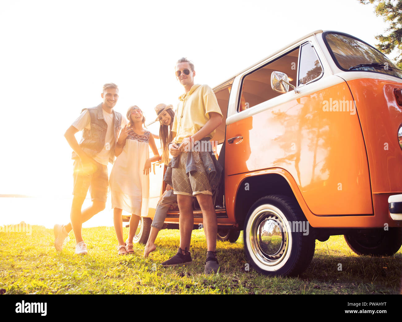 summer holidays, road trip, vacation, travel and people concept - smiling young hippie friends having fun over minivan car. - Stock Image