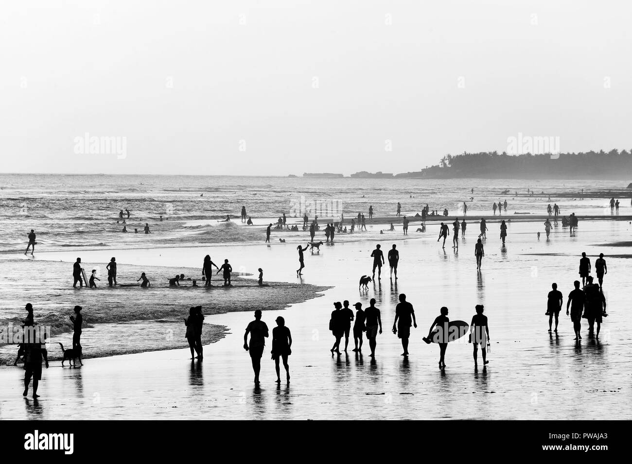 People walking on the ocean beach. Black and white. Bali island, Indonesia - Stock Image