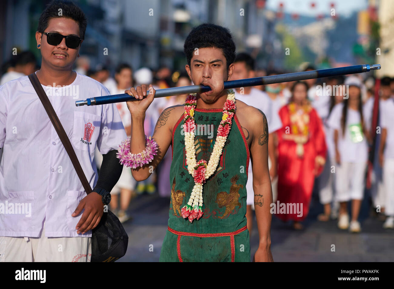 A spirit medium with his cheek pierced as part of the rituals during the Vegetarian Festival in Phuket, Thailand, in procession through Phang-Nga Rd. - Stock Image