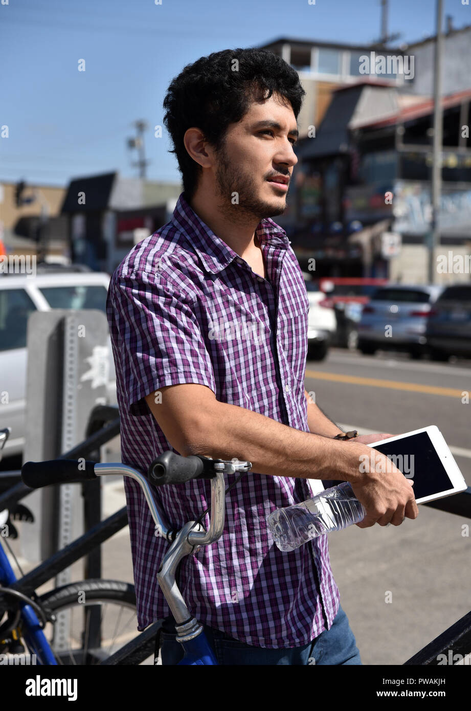 Attractive young generation z young man leaning against a bike rack in a laid back beach town. - Stock Image
