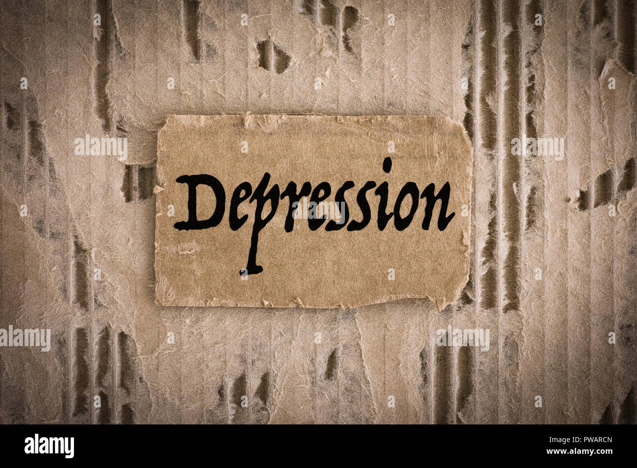 Piece of cardboard with word Depression on tattered corrugated cardboard background. Close-up. - Stock Image