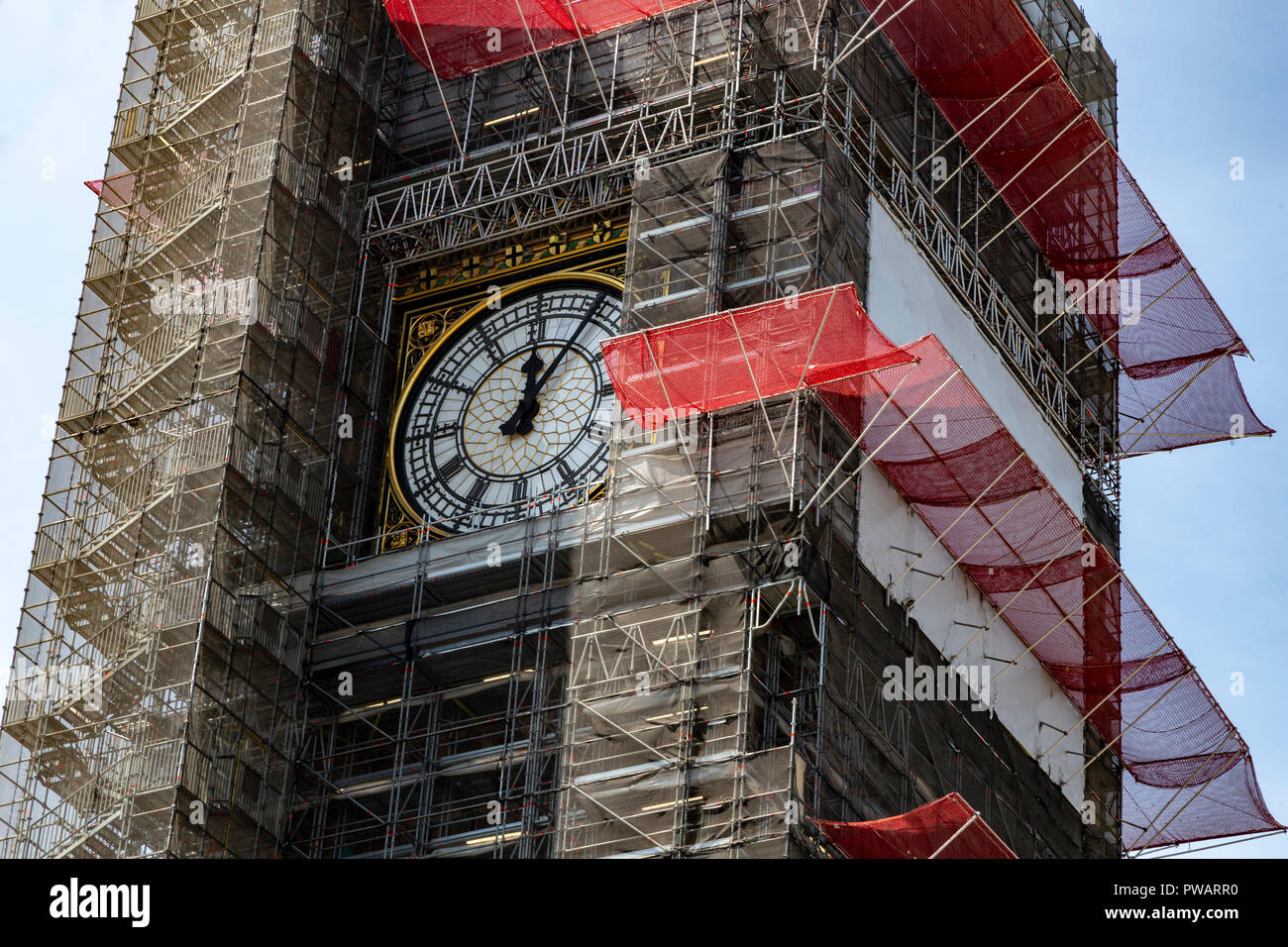 Big Ben clock still working while the tower is covered in scaffolding during refurbishment of the Houses of Parliament, London, UK - Stock Image