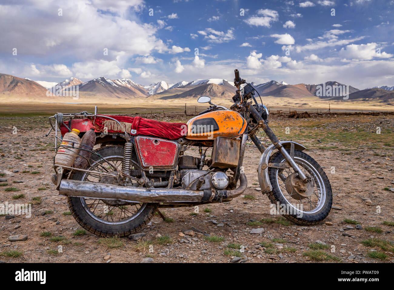 Old Russian HHH motorcycle with the Afghan Great Pamir in the background, Kara Jilga, Pamir Mountains, Gorno-Badakhshan, Tajikistan. - Stock Image