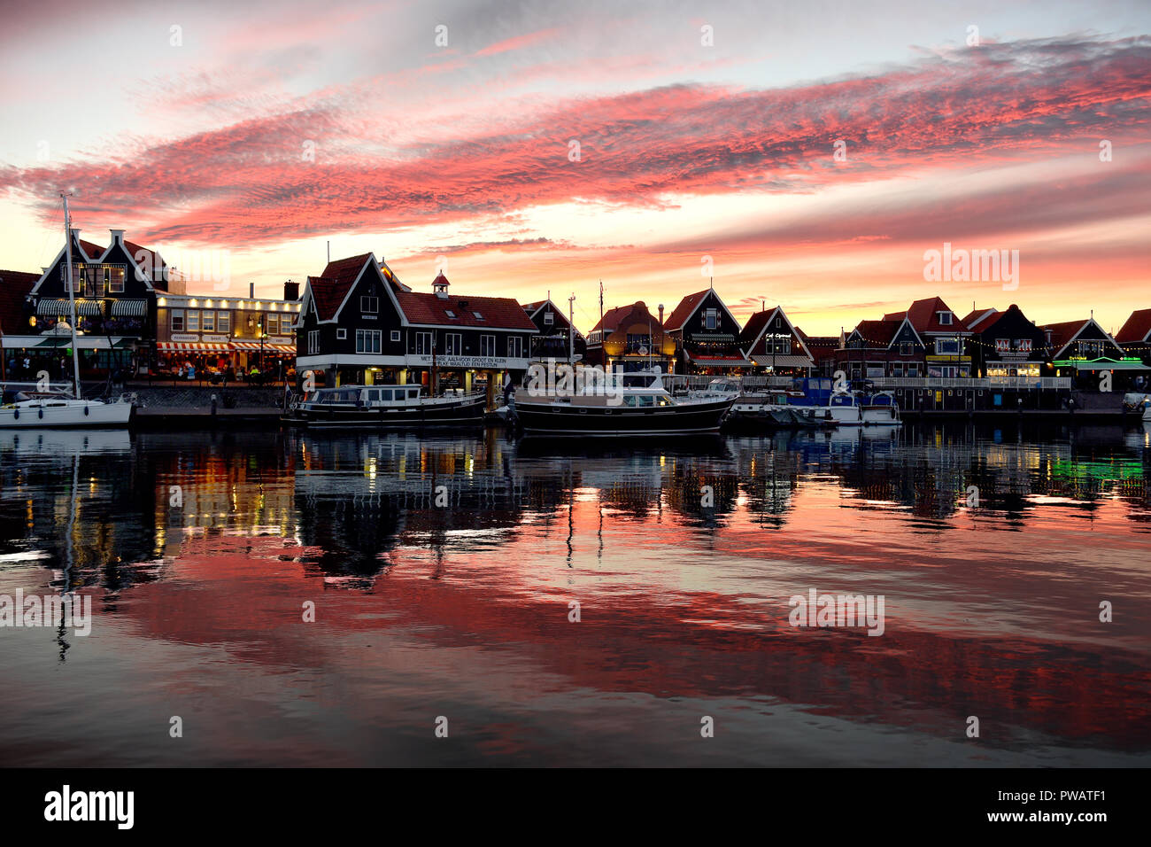 A charming red sunset over Volendam harbor - Stock Image