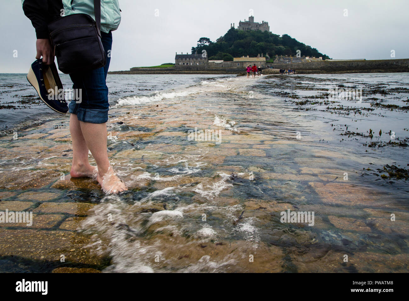 Barefooted female tourist crossing the causeway to St. Michael's Mount while it is being flooded by the high tide, Cornwall, UK - Stock Image