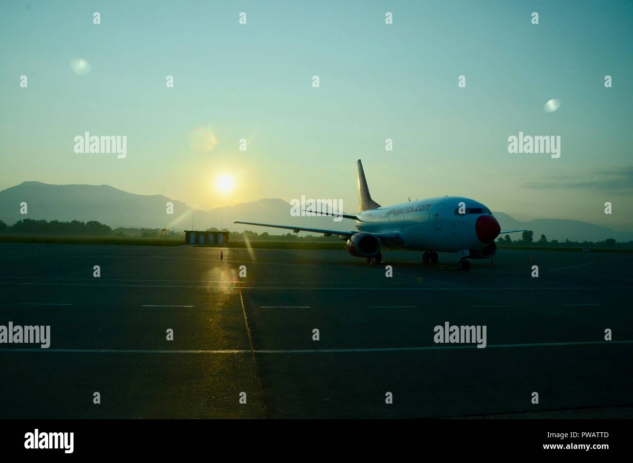 an albawings.com airplane on the tarmac at tirana airport at sunrise - Stock Image