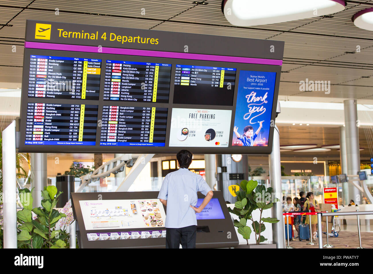 A man checking out Changi Airport Terminal 4 airlines flight information display system departure timing. T4 is the newest airport opens in 2018. - Stock Image