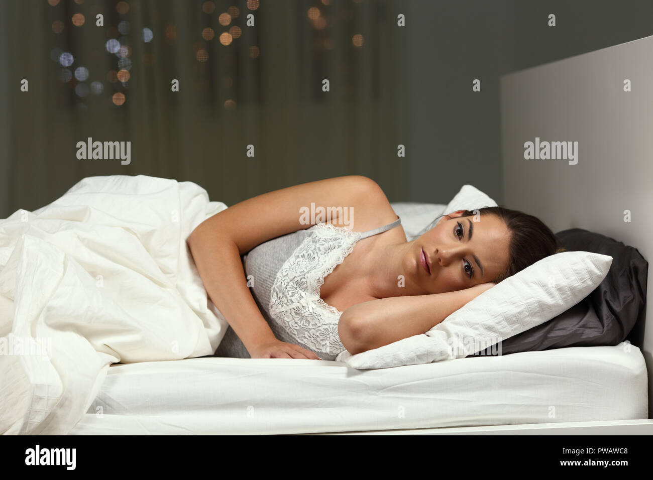 Insomniac woman can not sleep lying on the bed in the night at home - Stock Image