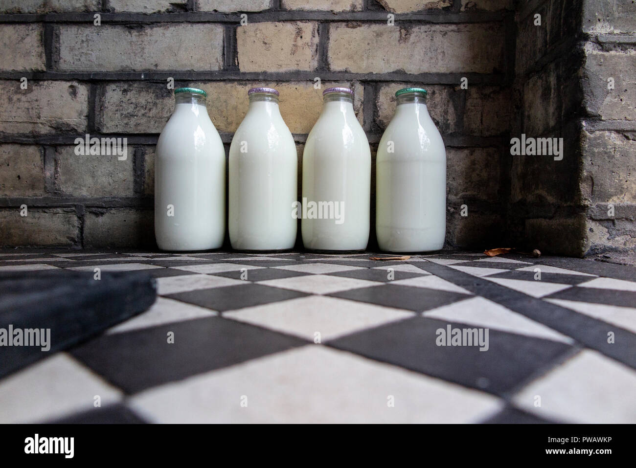 Four milk bottles on a doorstep of a terraced house in London - Stock Image