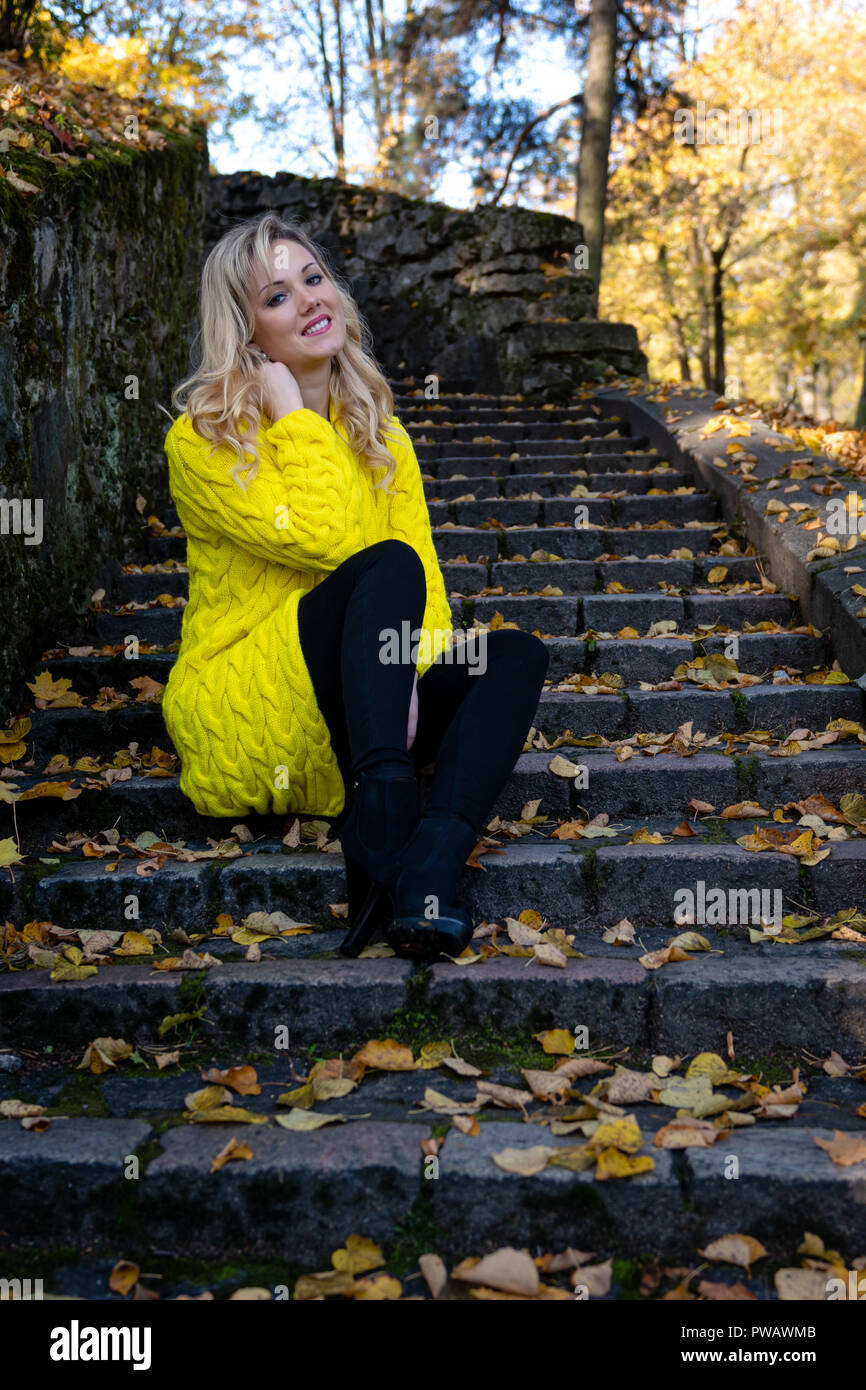 Young Beautiful Blonde Woman Sits In The Park On A Old Ladder