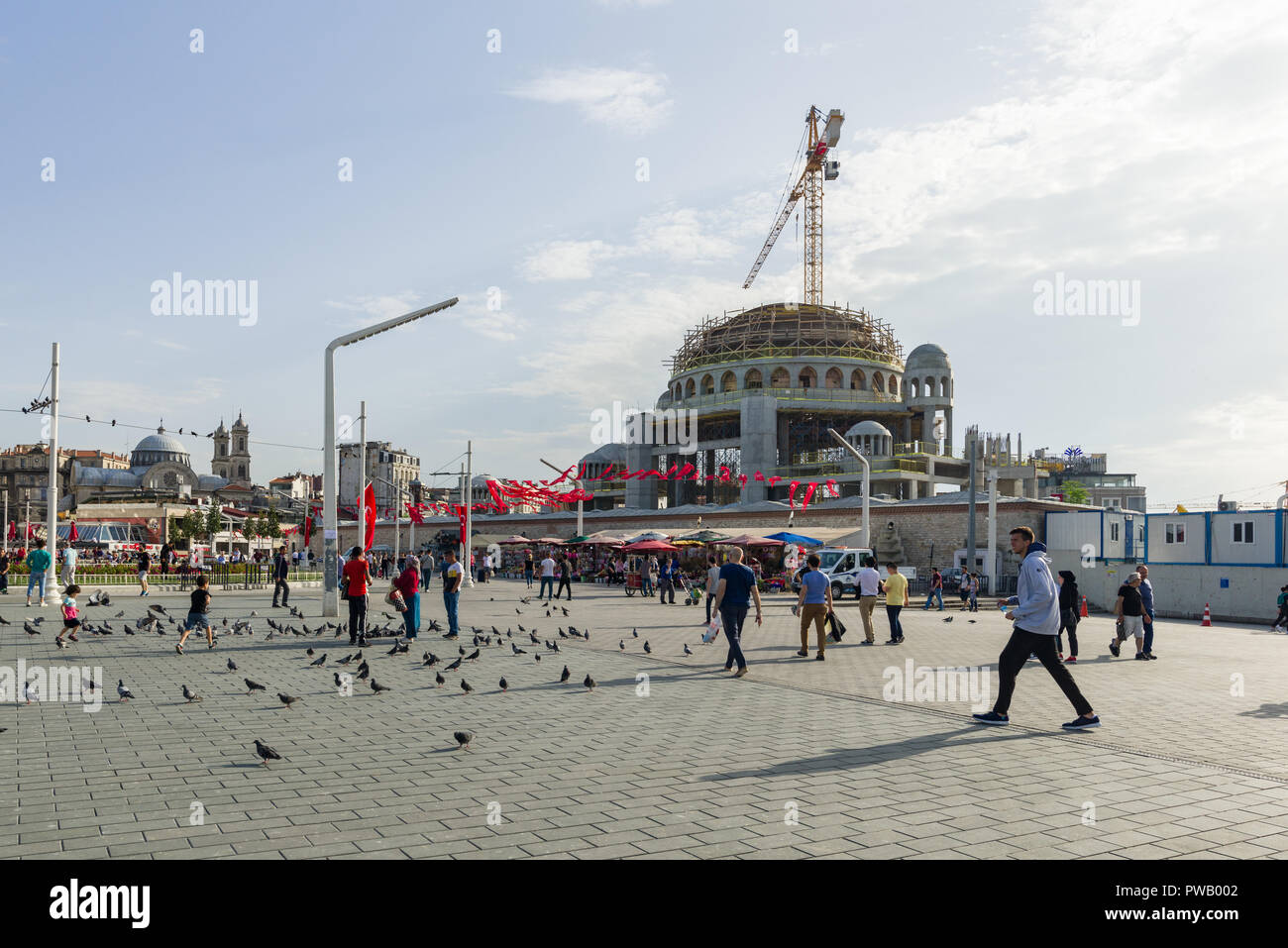 A mosque under construction near Taksim Square as people walk past, Istanbul, Turkey - Stock Image