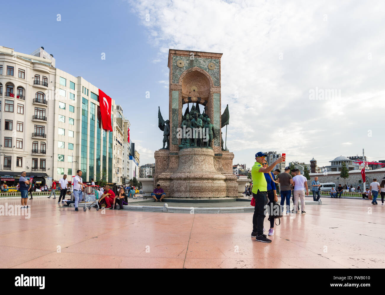 Locals and tourists at the Taksim Square memorial statue on a sunny Spring day, Istanbul, Turkey - Stock Image