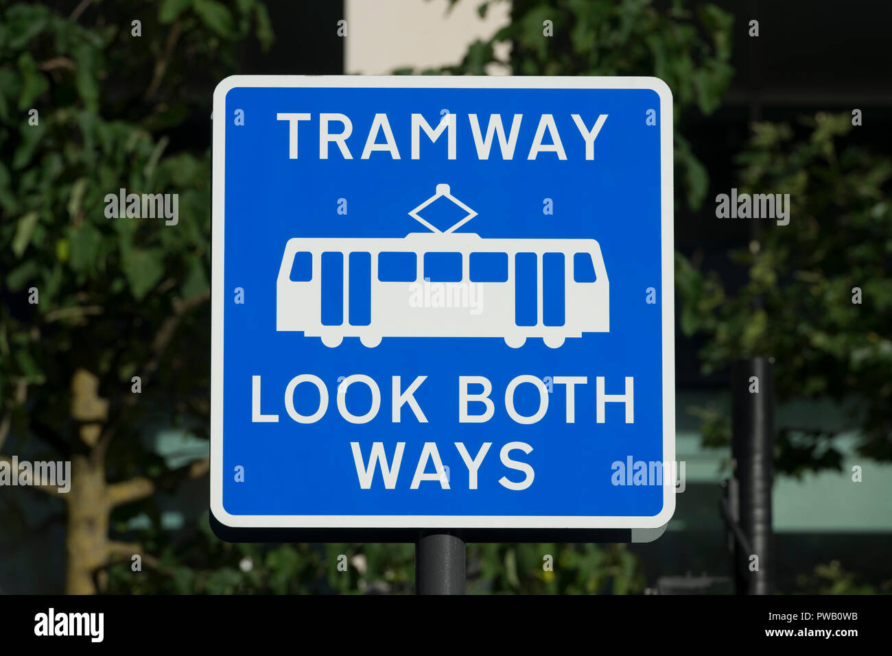 A sign reads 'Tramway Look Both Ways' in St Peter's square in Manchester, referring to the city's Metrolink system. - Stock Image