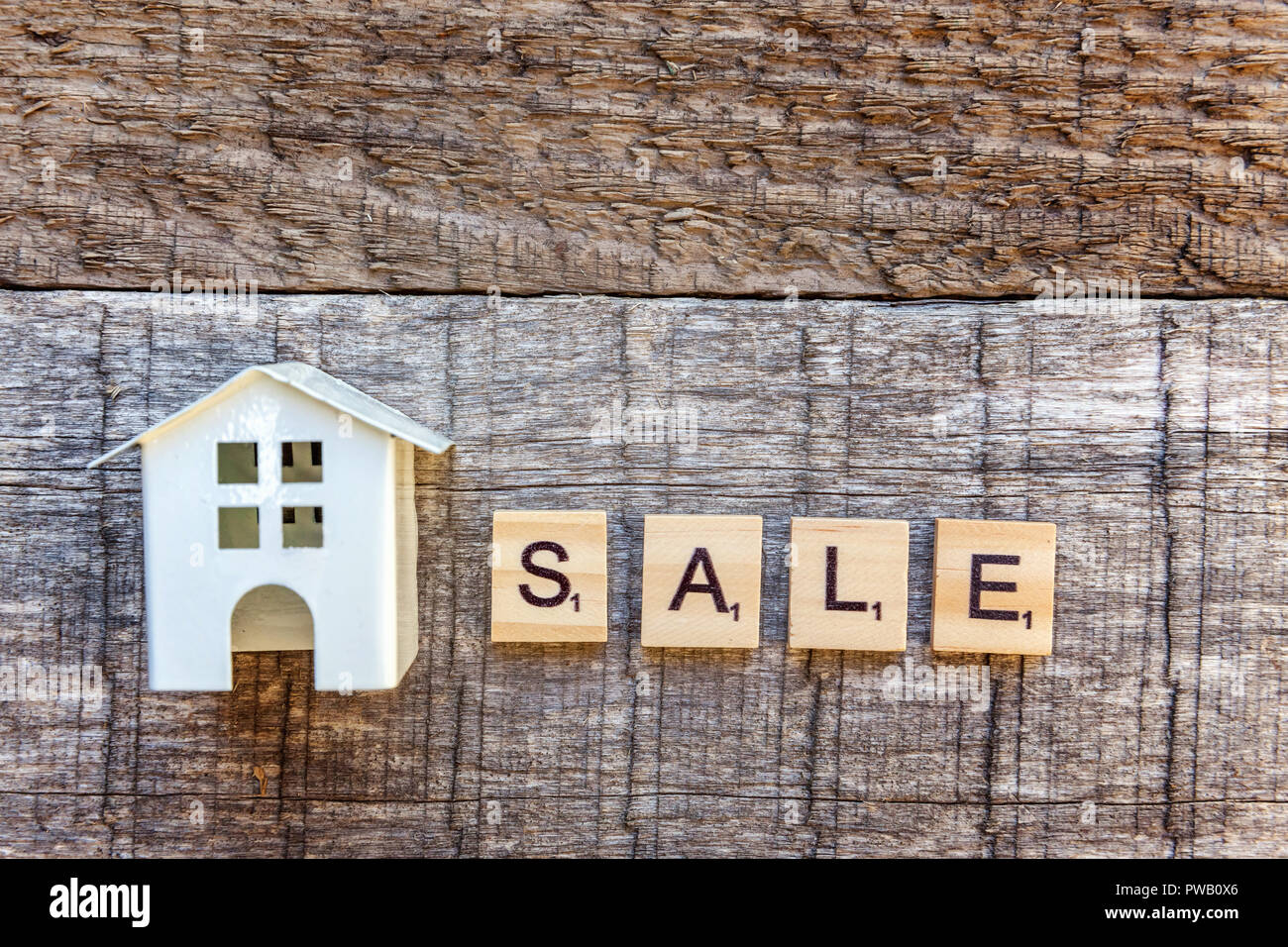 Miniature toy model house with inscription SALE letters word on wooden backdrop. Eco Village, abstract environmental background. Real estate mortgage  - Stock Image