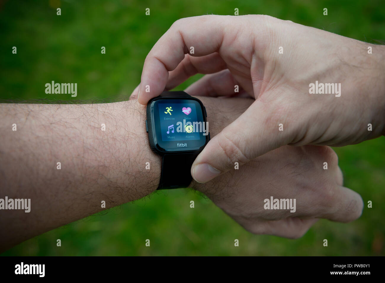 A men checks his Fitbit Versa activity tracker including heart rate