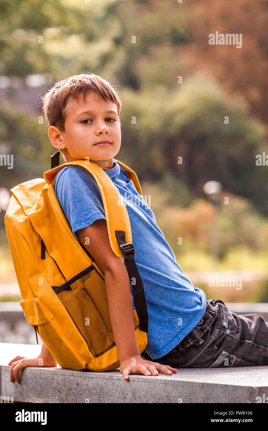4e42ea63c6a Kid with backpack sitting outdoors and looking to camera Stock Photo ...