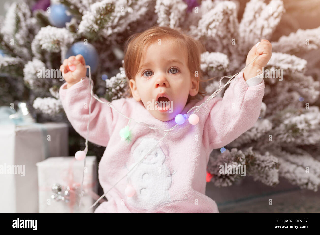 A little girl is playing with a garland with a New Year tree. Danger. Disobedient child. Good New Year spirit. - Stock Image
