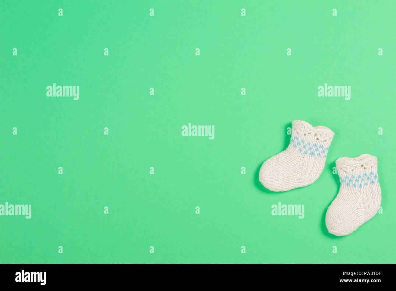 Knitted baby wool socks on green background - Stock Image