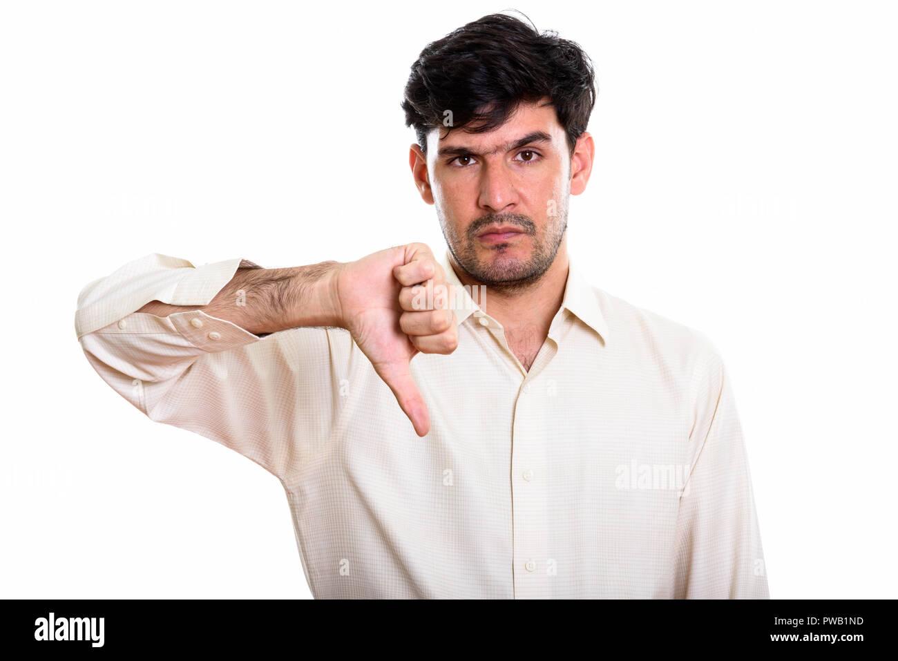 Studio shot of young Persian businessman  giving thumb down - Stock Image