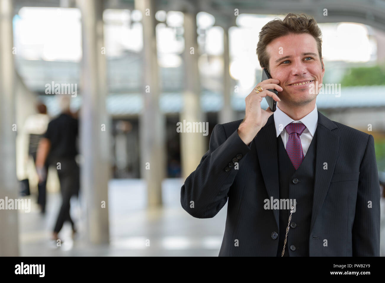 Happy thoughtful businessman smiling and talking on mobile phone - Stock Image