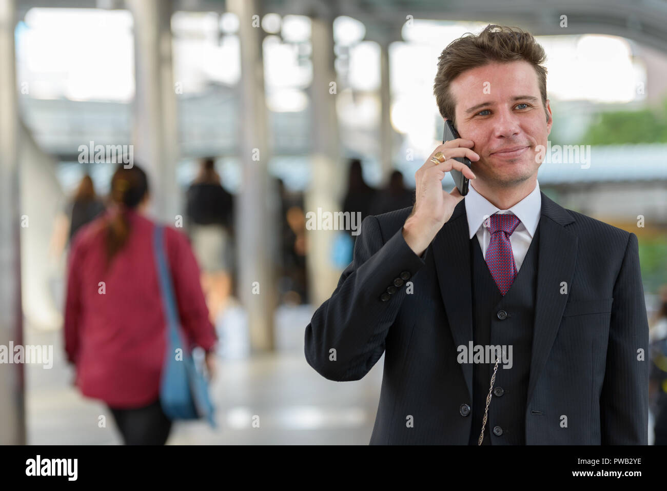 Businessman talking on mobile phone while thinking on train stat - Stock Image