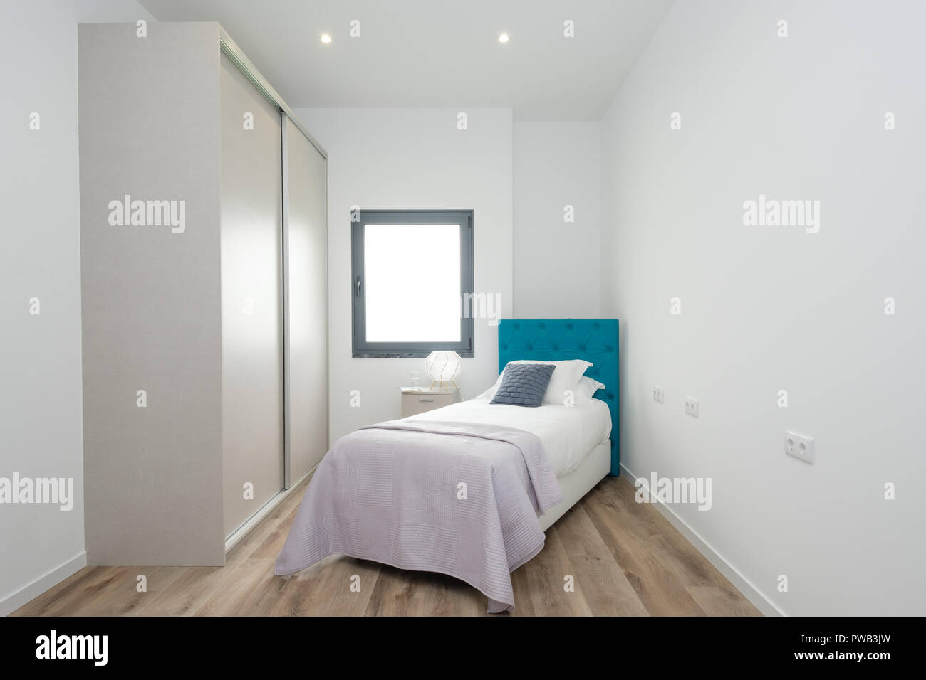 Small bedroom with a single bed, large wardrobe and a window Stock ...