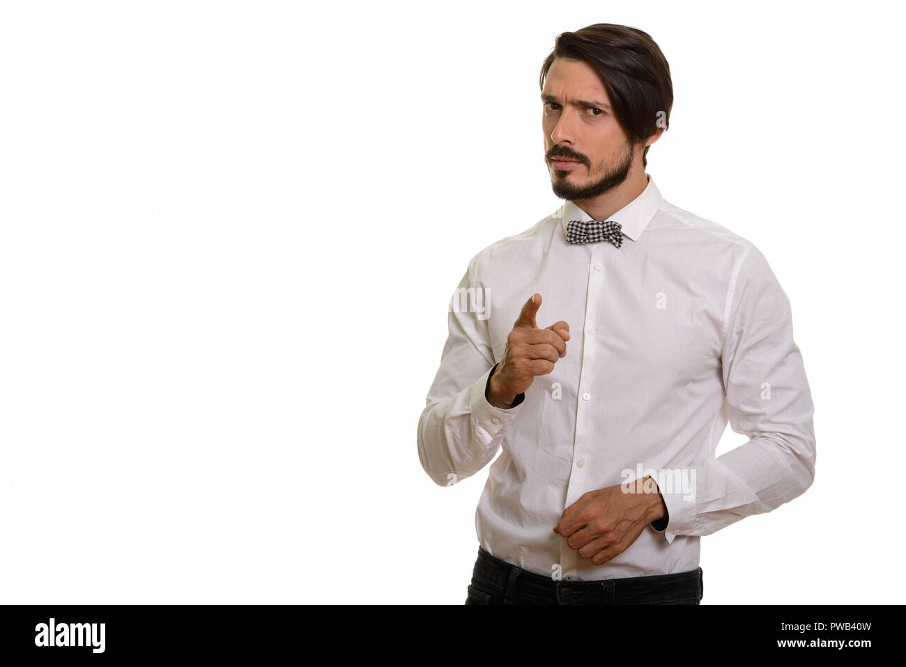 Studio shot of handsome man looking angry while pointing finger  - Stock Image