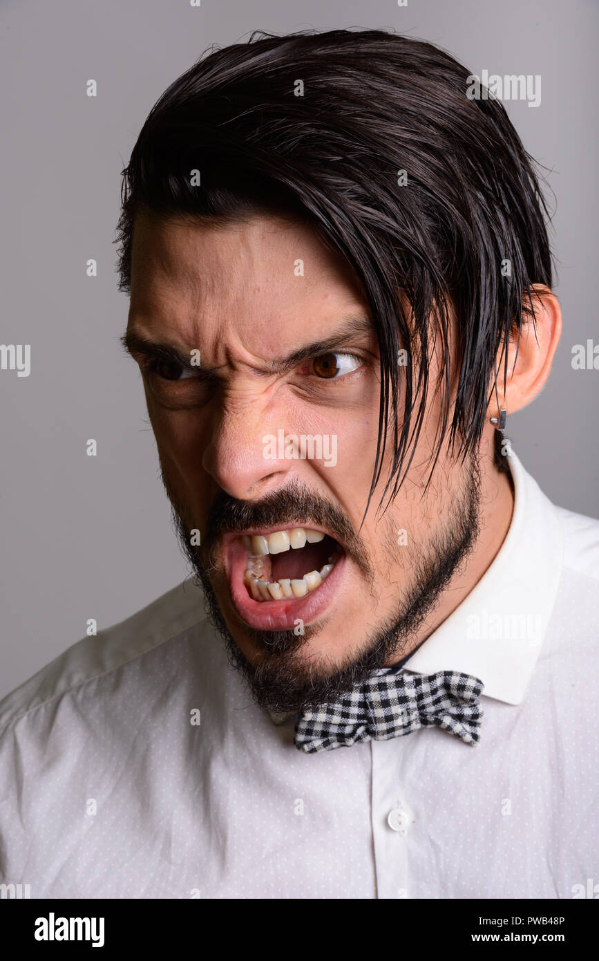 Face of handsome man looking furious against gray background - Stock Image