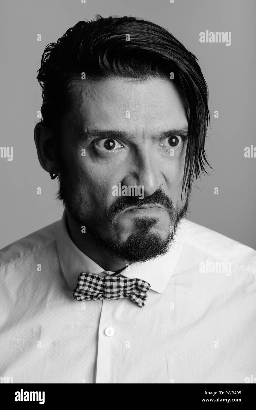 Face of handsome man looking angry in black and white - Stock Image